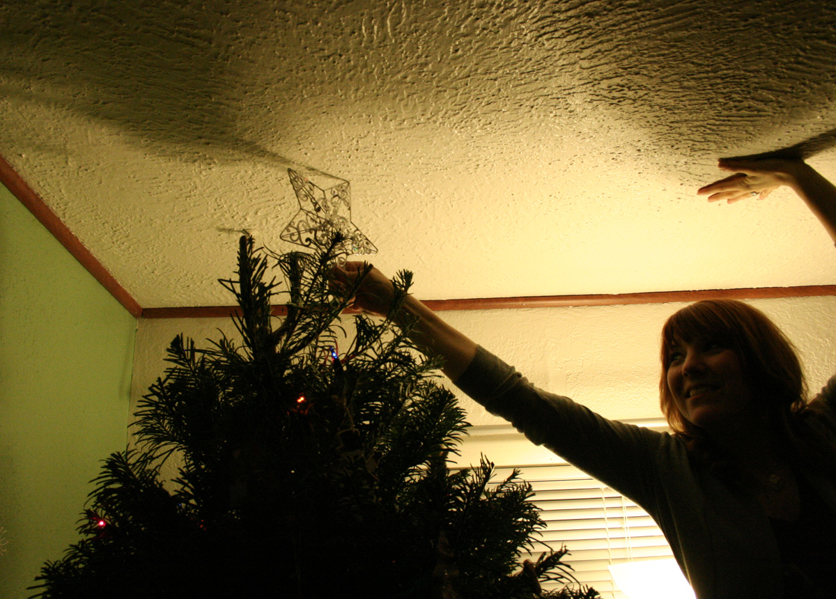 ..final touch, the star - it was a pretty tall tree, did I mention that?  After a couple attempts by Veda being hoisted up by Mark, I decided to give it a try.. I can still visualize myself falling into the tree, that would've put a damper on things just a bit...
